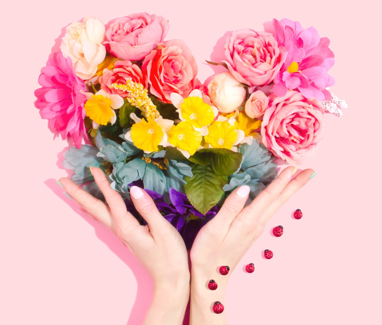 Open female hands holding bouquet of flowers in heart shape, with lady birds