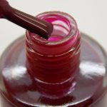 Close up off brush and bottle of LivOliv scarlett red nail polish